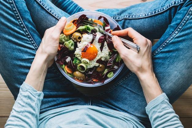 Erntenperson, die salat mit spiegelei isst