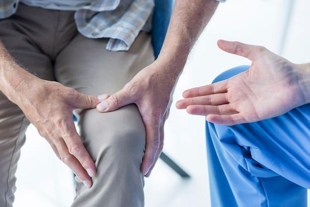 Erntepatient, der dem doktor schmerzendes knie zeigt