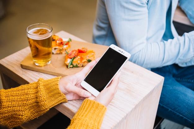 Erntet weibliche hände, die smartphone halten
