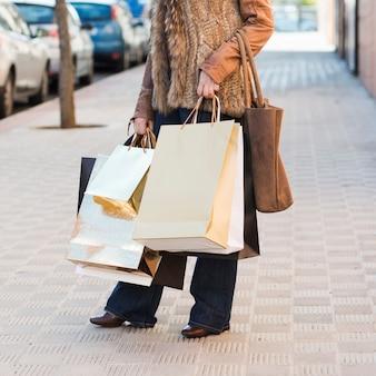 Erntet weibliche tragende helle Einkaufstaschen