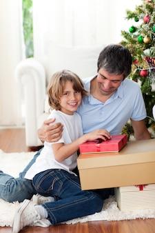 Eröffnende weihnachtsgeschenke des kleinen jungen mit seinem vater