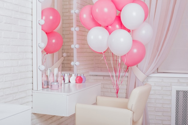 Eröffnung des schönheitsstudios - der arbeitsplatz ist mit rosa und weißen luftballons dekoriert.