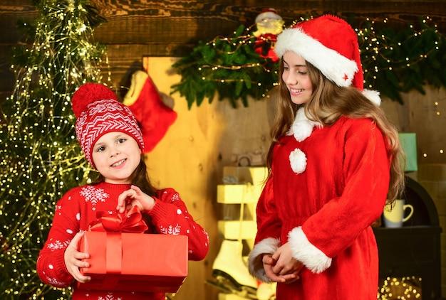 Eröffnung weihnachtsgeschenk. freundschaft. glückliche kinder geschenkbox. weihnachtseinkaufszeit. frohes neues jahr. zwei schwestern tauschen geschenke an weihnachten aus. kleine sankt-mädchen im zimmer. familienfeiertag.