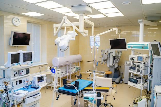 Eröffnungsaufnahme des technologisch fortschrittlichen operationssaals, der für die operation bereit ist. echter moderner operationssaal mit arbeitsgeräten, beleuchtung und computern.