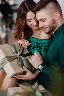Eröffnungsgeschenk. paare in der glücklichen liebe genießen feiertagsfeier. liebevolle lächelnde paarumarmung beim auspacken des geschenkbaumhintergrundes. was für eine überraschung.