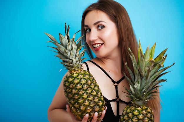 Erotische frau in einem gestreiften badeanzug und hohen absätzen bedeckt ihre brüste mit zwei ananasfrüchten