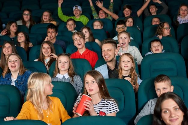 Erregte kinder, die im kino sitzen.