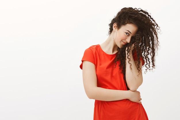 Errötende flirty frau im roten kleid, bedeckt die hälfte des gesichts mit lockigem haar und starrt mit einem auge