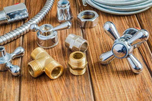 Ersatzteile mit kupfer- und kunststoffzubehör für die sanitärreparatur auf vintage-holzplatten