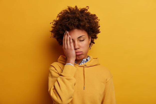 Erschöpfte afroamerikanische frau bedeckt halbes gesicht, müde, den ganzen tag zum testen zu üben, hat überarbeiteten ausdruck