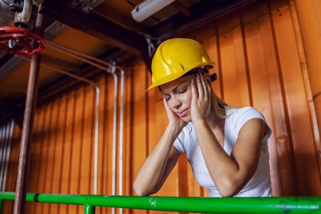 Erschöpfte arbeiterin mit schutzhelm auf dem kopf, der sich auf das geländer in der fabrik stützt und kopfschmerzen hat, weil sie überarbeitet ist.