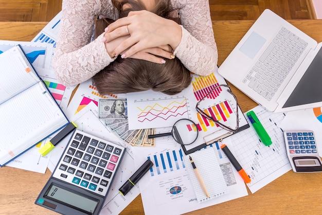 Erschöpfte business analystin schläft an ihrem arbeitsplatz