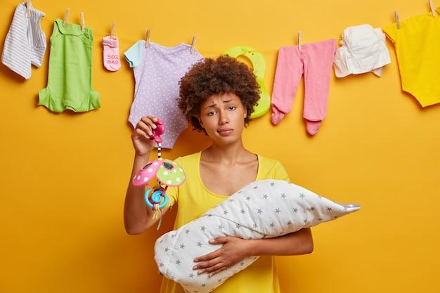 Erschöpfte ethnische mutter verbringt wertvolle zeit mit neugeborenen, hält mobil, hat ein müdes aussehen, müdigkeit schlafloser nächte und säuglingspflege. szene des schutzes und der liebe. mutterschaftskonzept