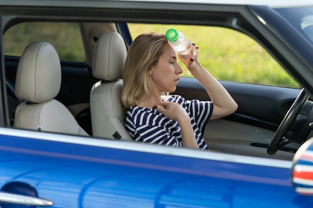 Erschöpfte fahrerin, die an kopfschmerzen leidet, hitze heißes wetter trägt eine flasche wasser auf die stirn