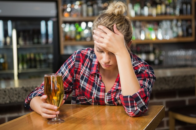Erschöpfte frau, die ein bier trinkt