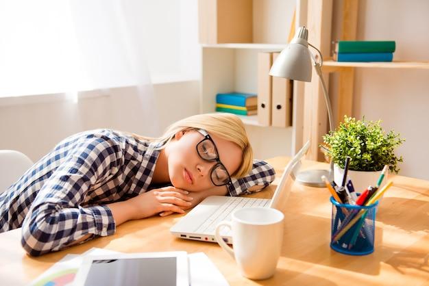 Erschöpfte frau, die nach hartem arbeitstag im büro schläft