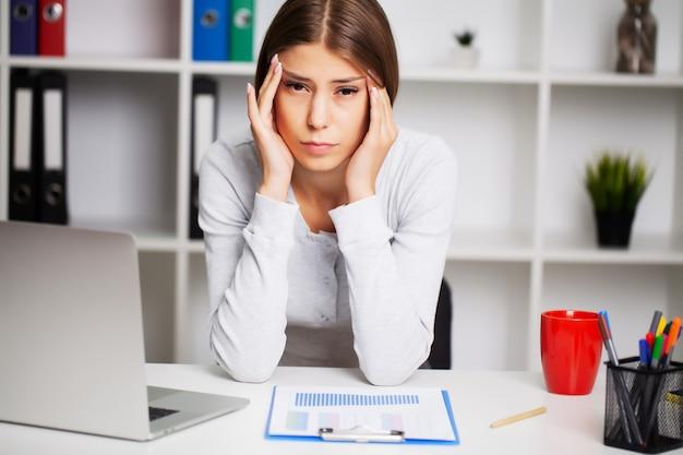 Erschöpfte frau im büro, die unter starken kopfschmerzen leidet