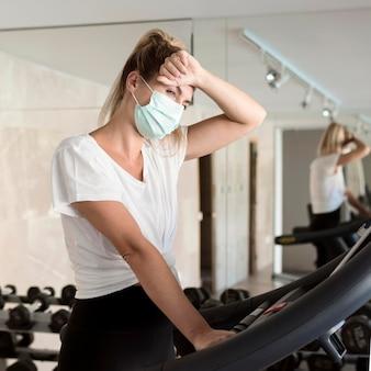 Erschöpfte frau mit medizinischer maske im fitnessstudio