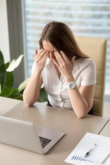 Erschöpfte geschäftsfrau, die am schreibtisch im büro sitzt