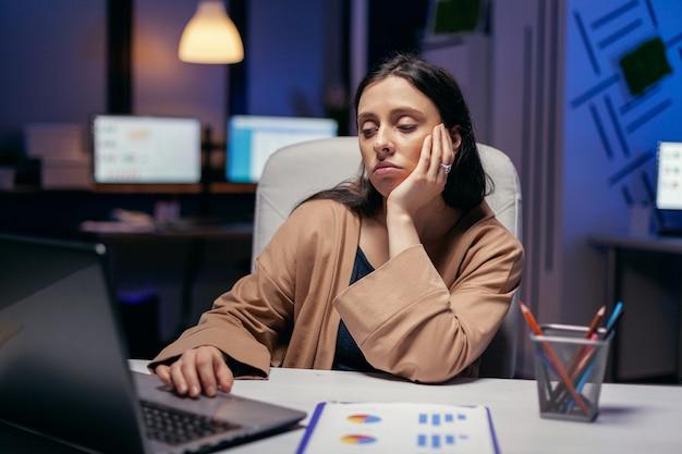 Erschöpfte geschäftsfrau, die computer arbeitet, um eine frist zu beenden. intelligente frau, die im laufe der späten nachtstunden an ihrem arbeitsplatz sitzt und ihren job macht.