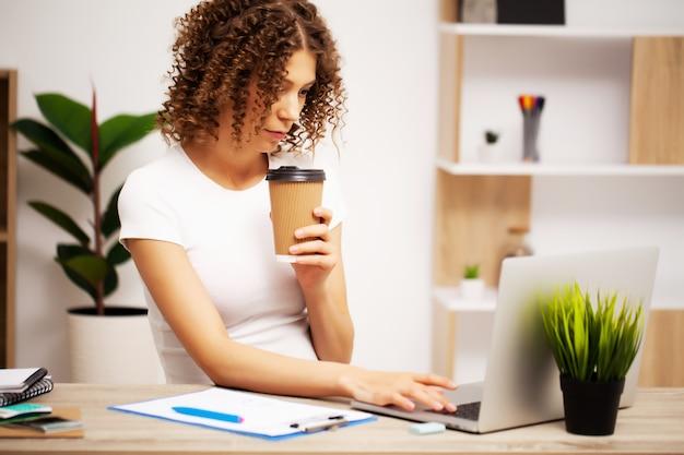Erschöpfte geschäftsfrau, die im büro auf einem laptop arbeitet