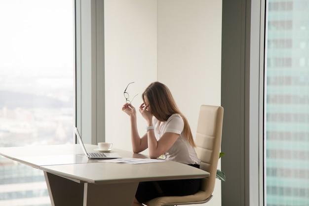 Erschöpfte geschäftsfrau, die im büro sitzt