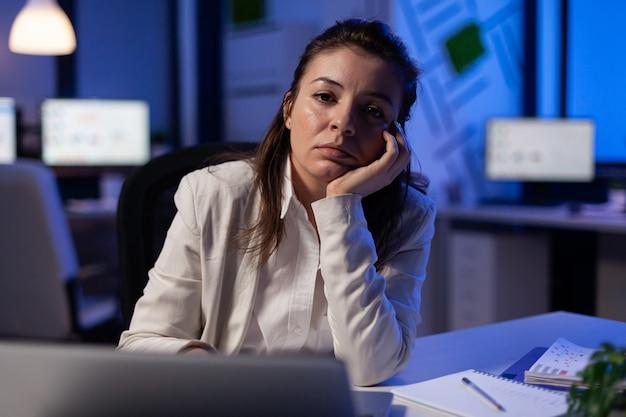 Erschöpfte geschäftsfrau, die spät in der nacht im geschäftsbüro müde in der kamera schaut und den kopf in der handfläche seufzt