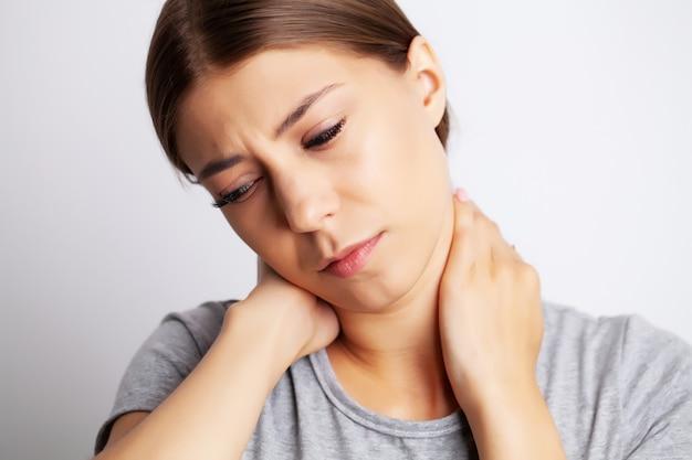 Erschöpfte junge frau, die unter starken nackenschmerzen leidet