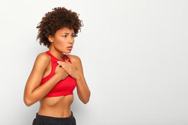 Erschöpfte lockige frau leidet an asthma-atemproblemen, hält beide hände auf der brust und trägt ein rotes oberteil
