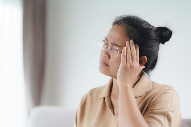 Erschöpfte müde deprimierte gestresste nachdenkliche reife ältere frau, die an kopfschmerzen, gehirnerkrankungen, psychischen problemen, alzheimer-konzept leidet.