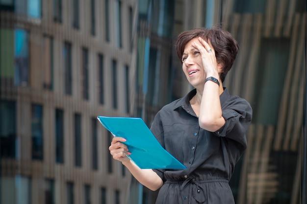 Erschöpfte, müde, frustrierte, überarbeitete geschäftsfrau, schöne, negativ überladene dame mit dokumenten, papieren.