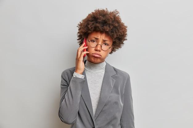 Erschöpfte traurige geschäftsfrau mit lockigem haar, telefoniert, trägt ein trendiges formelles outfit, unterhält langweilige gespräche, sieht unglücklich aus und seufzt vor müdigkeit