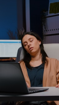 Erschöpfte unternehmerin, die vor dem laptop schläft, während sie finanzstatistiken analysiert
