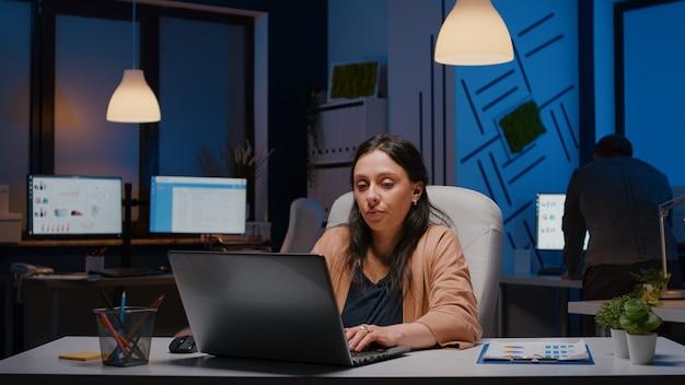 Erschöpfte workaholic-geschäftsfrau, die finanzgrafiken auf laptop analysiert