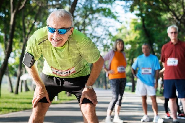 Erschöpfter älterer läufer am park