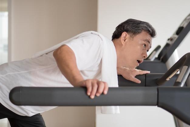 Erschöpfter älterer mann, der unfall im fitnessstudio hat