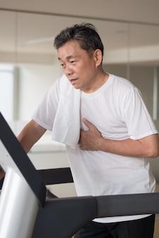 Erschöpfter älterer mann in der fadenmühle im fitnessstudio