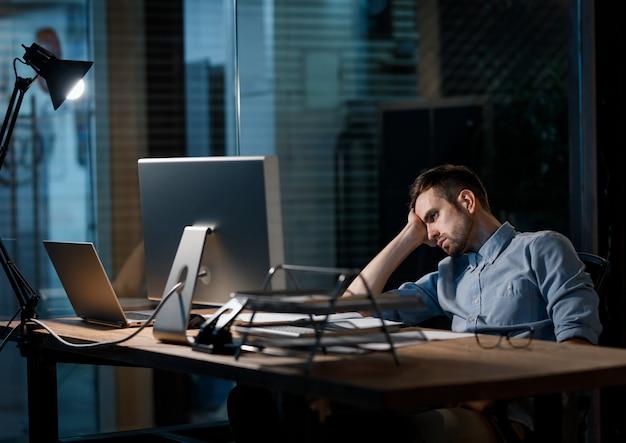 Erschöpfter arbeiter beobachtet computer