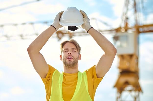 Erschöpfter arbeiter mit geschlossenen augen, der seinen helm über dem kopf hält