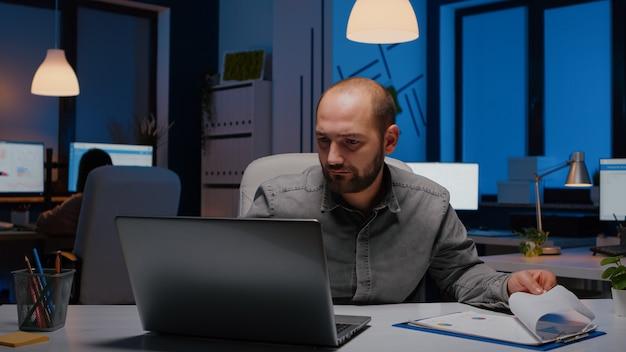 Erschöpfter arbeitssüchtiger geschäftsmann, der marketingstatistiken analysiert, die am schreibtischtisch sitzen
