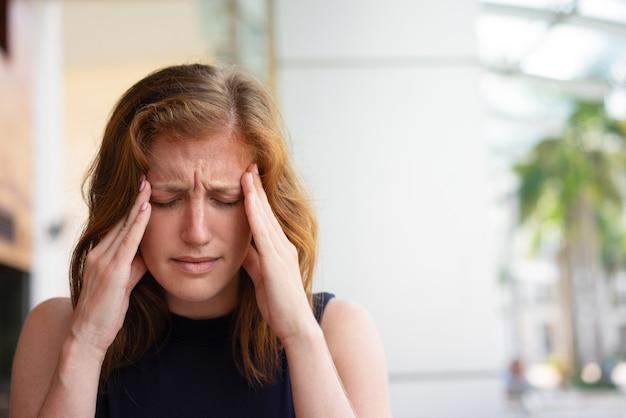 Erschöpfter büroangestellter, der unter kopfschmerzen leidet