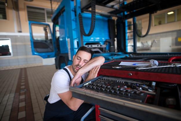 Erschöpfter fahrzeugmechaniker schläft in seiner werkstatt ein