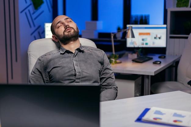 Erschöpfter fleißiger geschäftsmann, der auf stuhl schläft workaholic-mitarbeiter schläft ein, weil er spät nachts allein im büro für ein wichtiges unternehmensprojekt arbeitet.