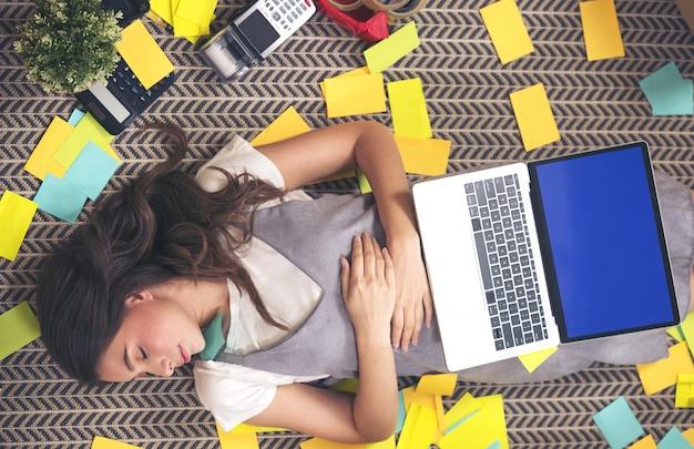 Erschöpfter freiberufler, der ein nickerchen macht, wenn er im home office auf dem boden schläft. attraktive frau zu hause