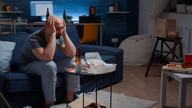 Erschöpfter frustrierter depressiver junger mann massiert schläfen mit psychischen problemen gestresst ungesund...
