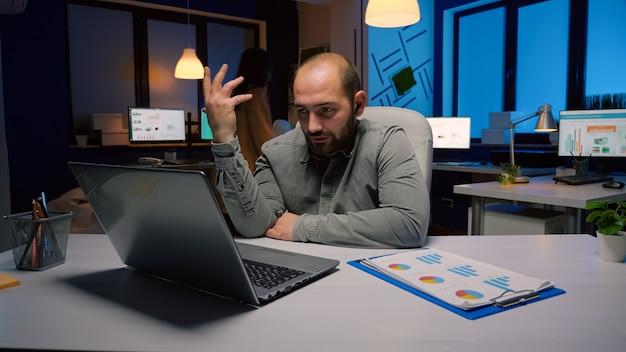 Erschöpfter geschäftsmann, der während der online-videokonferenz-konferenz das marketing-deadline-projekt mit einem remote-mitarbeiter bespricht. unternehmer, der spät in der nacht am schreibtisch im büro der geschäftsfirma sitzt