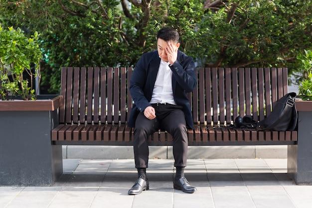 Erschöpfter junger asiatischer geschäftsmann, der draußen auf der bank im stadtpark sitzt. gestresster überarbeiteter mann mit kopfschmerzen massiert den kopf. depressiv müder mitarbeiter mit schmerzkranker arbeit