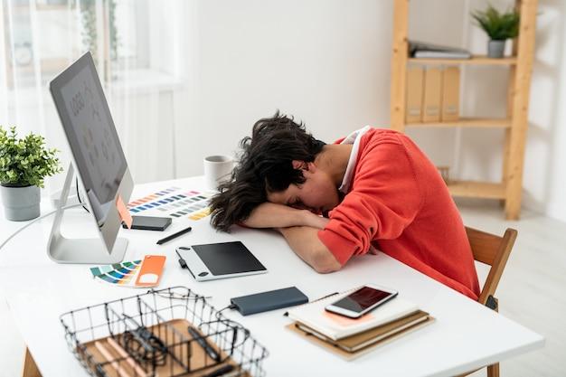 Erschöpfter junger männlicher freiberufler, der auf dem schreibtisch vor dem computerbildschirm zwischen arbeitsmaterial und geräten ein nickerchen macht