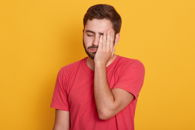 Erschöpfter junger unrasierter gesichtshälfte mit der hand im gelben studio, sieht müde aus und fühlt sich deprimiert