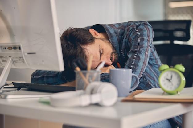Erschöpfter männlicher arbeiter, der am tisch mit computer und wecker im modernen büro schläft